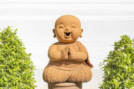 buddha statue: smiling buddhist novice sculpture in temple.