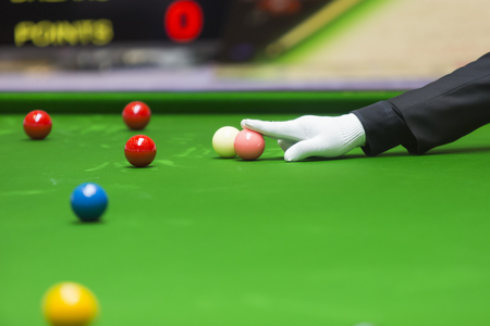 games hand: snooker referee put pink ball on point. Stock Photo