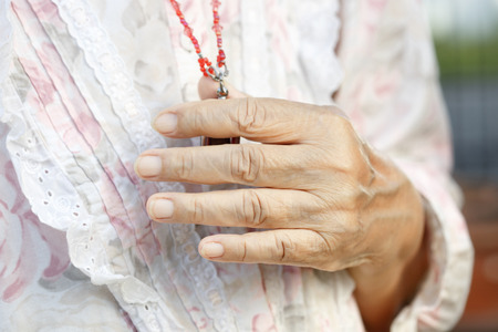relation: senior womans hands in pray to buddha. Stock Photo