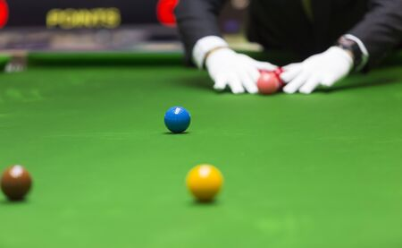 games hand: snooker referee arrange balls for new game , focus at blue ball