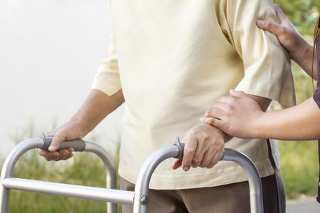mujer mayor con un andador con cuidador