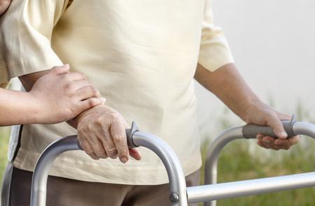 年配の女性が歩行器を用いた介護 写真素材