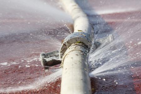 mangera: el desperdicio de agua - agua que se escapa del agujero en una manguera