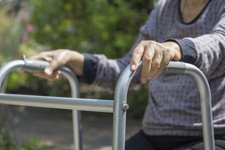 Elderly sitting in backyard with walker.