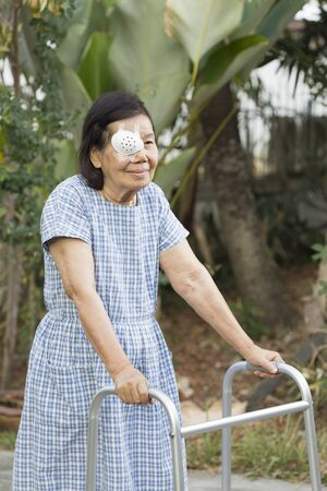 cataract: Elderly use eye shield covering after cataract surgery in backyard.