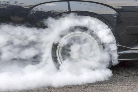 in the smoke: coche de carreras de resistencia quema de caucho de los neumáticos en la preparación para la carrera