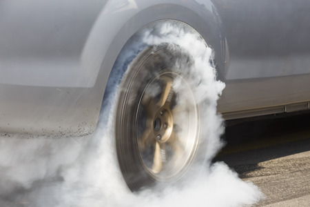 car on the road: Drag racing car burns rubber off its tires in preparation for the race Stock Photo