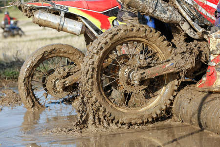 Enduro wheel in muddy track ,climb wood obstacle Banco de Imagens