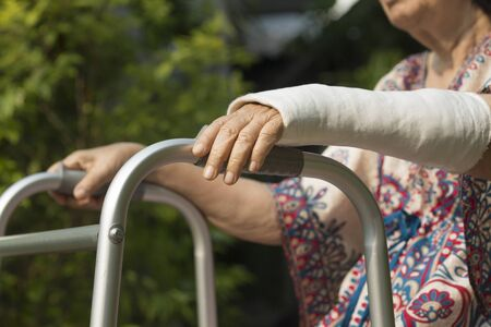 broken wrist: senior woman broken wrist using walker in backyard. Stock Photo