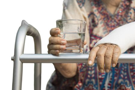 adult bones: senior woman broken wrist using walker in backyard. Stock Photo