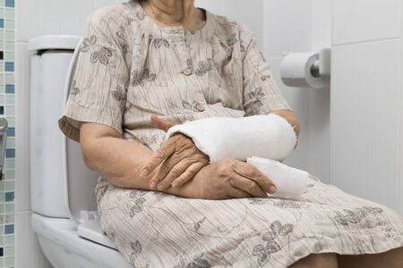 broken wrist: Senior women broken wrist using the toilet Stock Photo