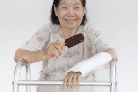broken wrist: elderly woman broken wrist enjoying ice cream Stock Photo