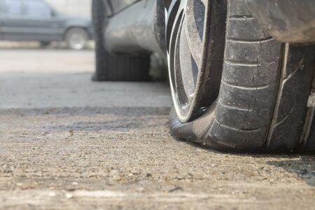 neumático desinflado coche en el camino