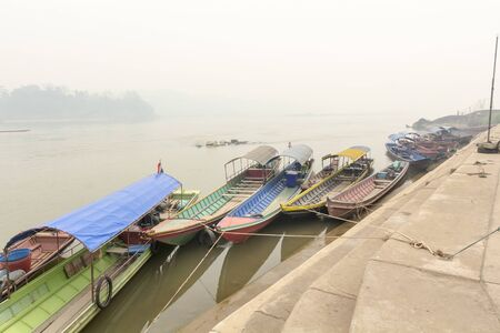 heavily: Heavily polluted air from forest fire cover Mekong river at chiang khong port Stock Photo