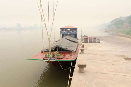 polluted river: Heavily polluted air from forest fire cover Mekong river at chiang khong port Stock Photo