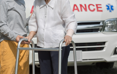 cross street with care: senior woman using a walker with caregiver to take ambulance