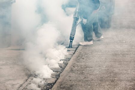 breeding ground: Worker fogging street drain with insecticides to kill aedes mosquito breeding ground, carrier of dengue and Zika virus Stock Photo