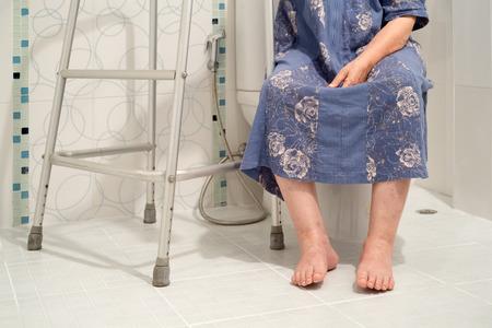 Senior women using the toilet with walker.