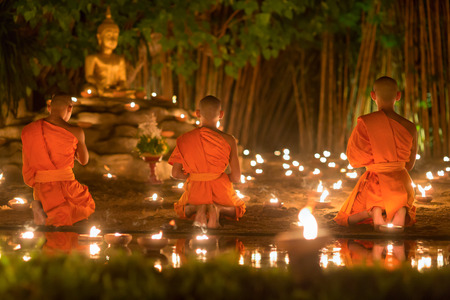 puja: Asalha Puja Day ,Monks light candles and pray to buddha statue in Phan tao temple , Chiang mai ,Thailand