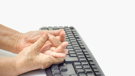 finger on trigger: Senior woman painful finger due to prolonged use of keyboard and mouse