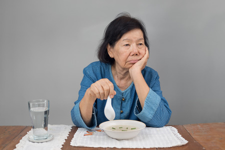 Ältere asiatische Frau gelangweilt mit dem Essen