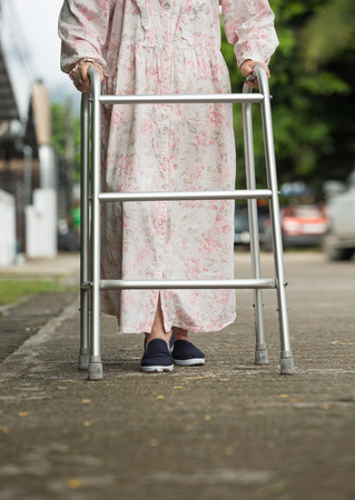 cross street with care: senior woman using a walker on street.