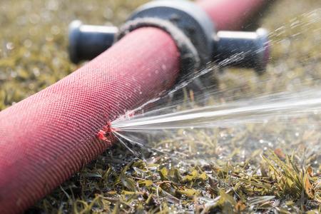 agua que se escapa del agujero en una manguera