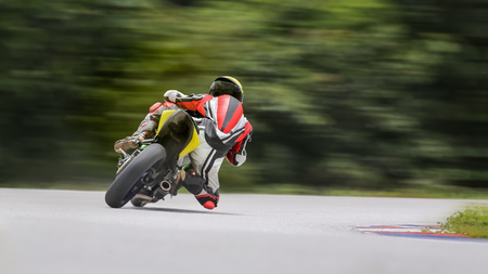 motor race: Motorcycle practice leaning into a fast corner on track