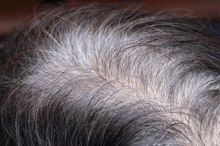 Ältere asiatische Frau zeigt ihr graues Haar