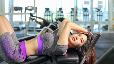 Asian woman doing sit ups fitness exercise at sport gym