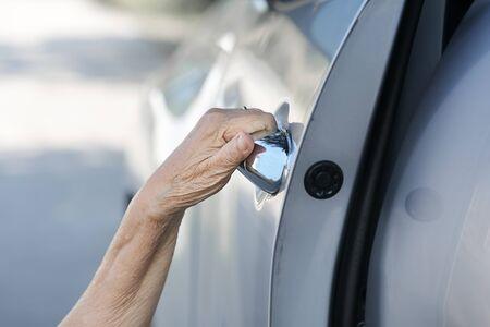 horizental: Elderly woman open door car Stock Photo