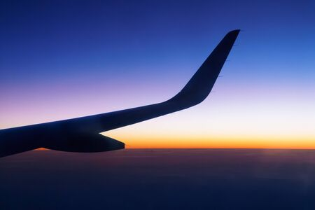 trave: Wing of plane on sunset sky and clouds
