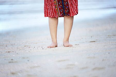 outstretching: Bare feet of tourist woman enjoying travel vacation in Krabi, Thailand.