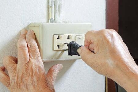 quivering: Elderly woman trying plug cable to the electric outlet Stock Photo