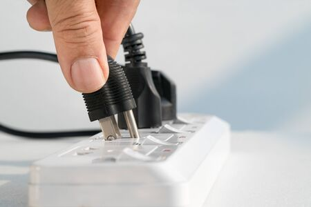 quivering: Close up Elderly hand plugging into electrical outlet Stock Photo