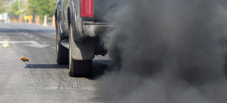 dirty car: Air pollution from vehicle exhaust pipe on road.