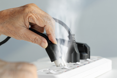 quivering: Elderly hand with electrical outlet spark