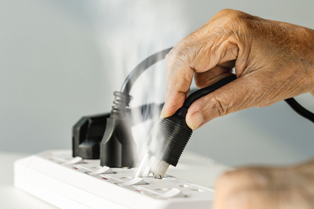 Elderly hand with electrical outlet spark