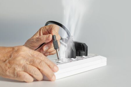 quivering: Elderly have a problem mistake plugging socket type to electrical outlet.