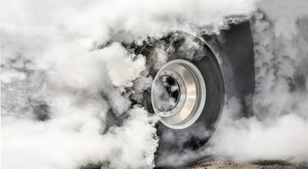Drag racing car burning tires at start line