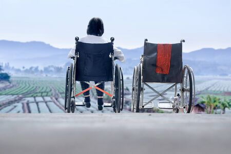 Elderly woman with empty wheelchair standing together