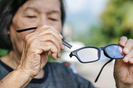 vision repair: Elderly asian woman repair broken glasses