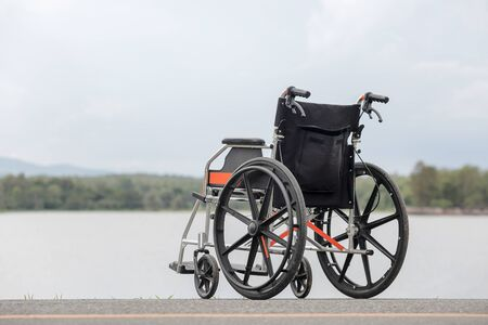 accidental: Empty wheelchair on lake Stock Photo