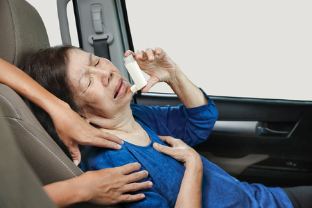 choking: Elderly woman choking and holding an asthma spray in car on the way Stock Photo