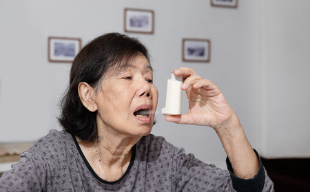 Elderly woman choking and holding an asthma spray