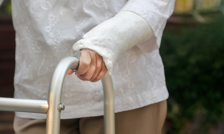 senior woman broken wrist using walker in backyard Stock Photo