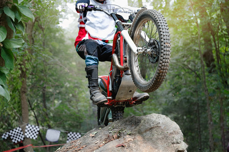 Trials motorcycle is jumping over rocks
