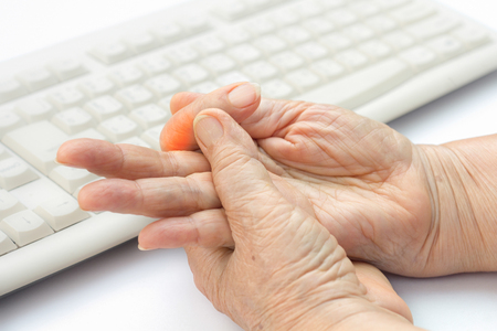 Senior woman painful finger due to prolonged use of keyboard and mouse.