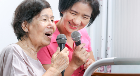 Elderly woman sing a song with daughter at home.