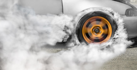 Drag racing car burns rubber off its tires in preparation for the race Stock Photo